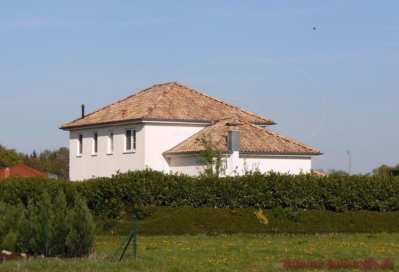 Weiß gestrichenes Haus mit bunten Dachziegeln die verschiedene Grautöne aufweisen