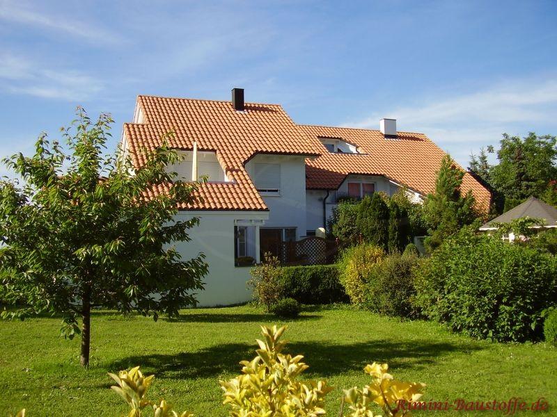 Gepflegter Garten im Sommer mit einem großem Haus im Hintergrund das gewölbte Ziegel auf dem Dach hat