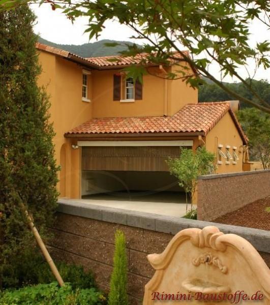 Aprikotfassade mit bunten Dachsteinen und Fensterläden. Es ist eine große Anbaugarage zu sehen