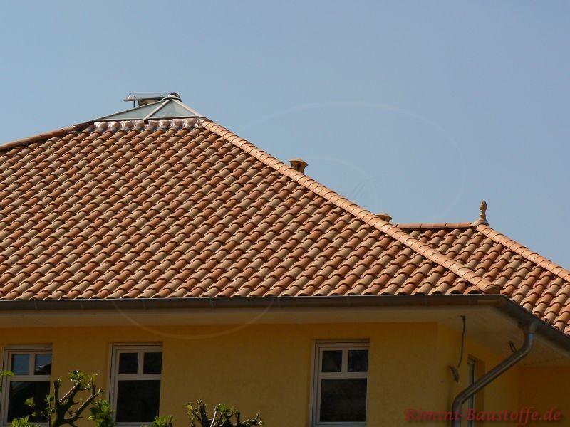 Großes Spitzdach mit Lichtkuppel. Die Dachziegel sind in zwei Farben und nach einem Muster verlegt worden