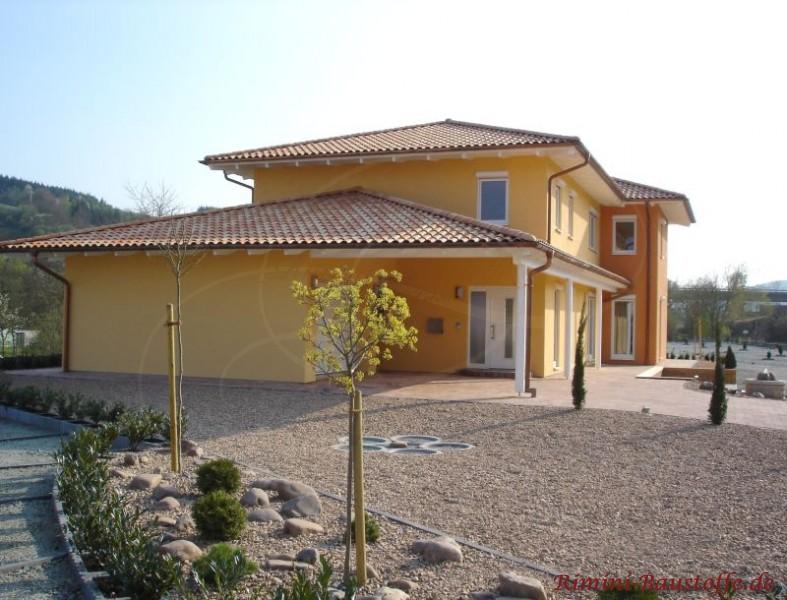 Toskanavilla mit hellem Putz und bunten Dachziegeln. Das Garagendach ist Verandaartig über die Haustür verlängert