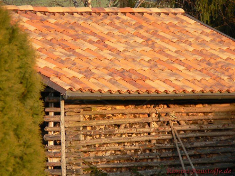 Kleiner Unterstand für Holz im mediterranem Stil bei Toskanasonne. Die Dachziegel haben eine schöne Farbe