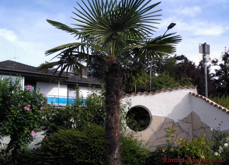 mediterrane Gartenmauer halbhoch in Natursteinoptik mit rundem Fenster
