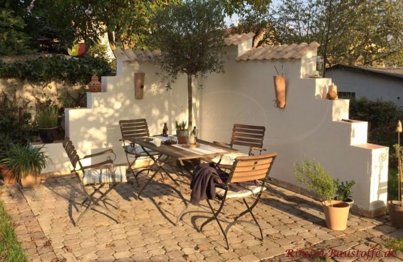 wunderschoene gemuetliche Sitzecke mit Winschutz in Form einer Mauer