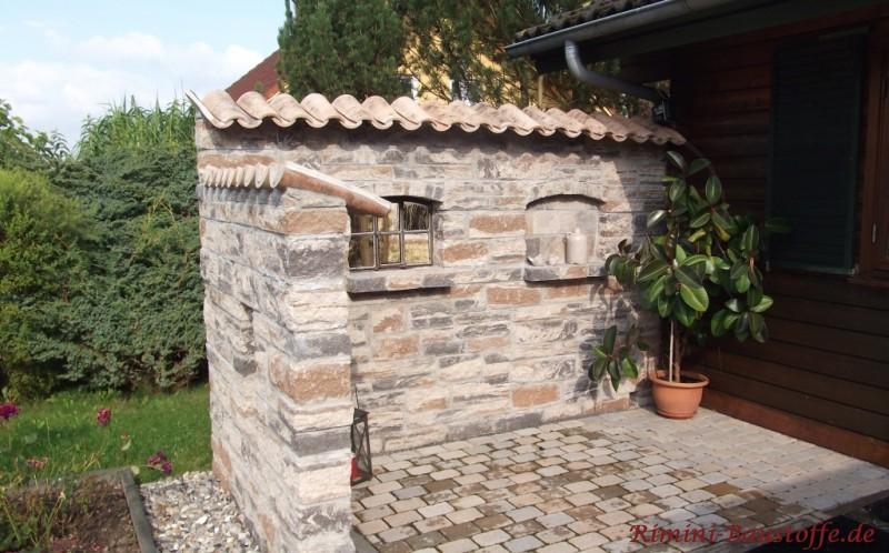 Natursteinmauer mit Moench Nonne Dachziegeln abgedeckt