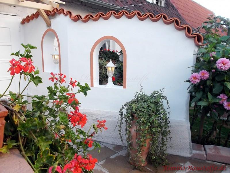 weisse Gartenmauer mit farbigen Faschen in der Farbe der Halbschalen