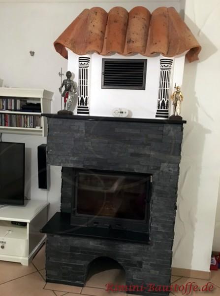 schwarz verblendeter Kamin im Wohnzimmer mit Halbschalen gedeckt