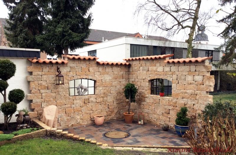 Gartenmauer in Natursteinoptik mit Gusseisenfenstern