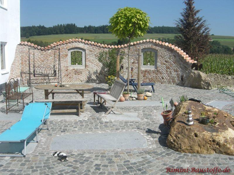 Terrasse mit rustikaler geschwungener Mauer, welche mit Dachziegeln bedeckt ist.