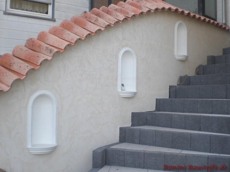 Ansteigende Treppenlauf mit Halbschalen aus Apanien abgedeckt. In der Wand sind drei weiße Dekobrunnen eingearbeitet