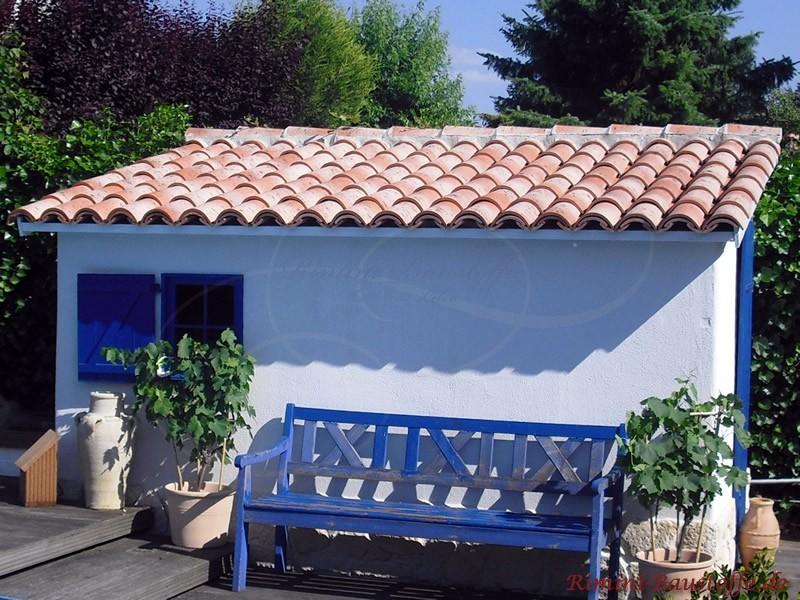 Mediterranes Gartenhäuschen mit weißer Fassade, blauer Sitzbank und blauen Fensterläden
