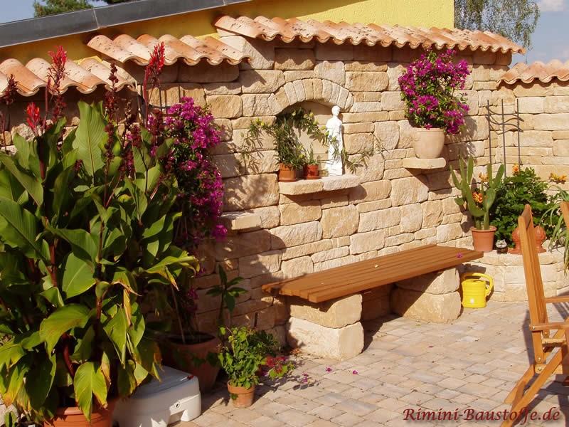 Schöne Sitzecke mit Natursteinen und Ziegeln. Eine Dekovase steht innerhalb der Wand in einer Vertiefung