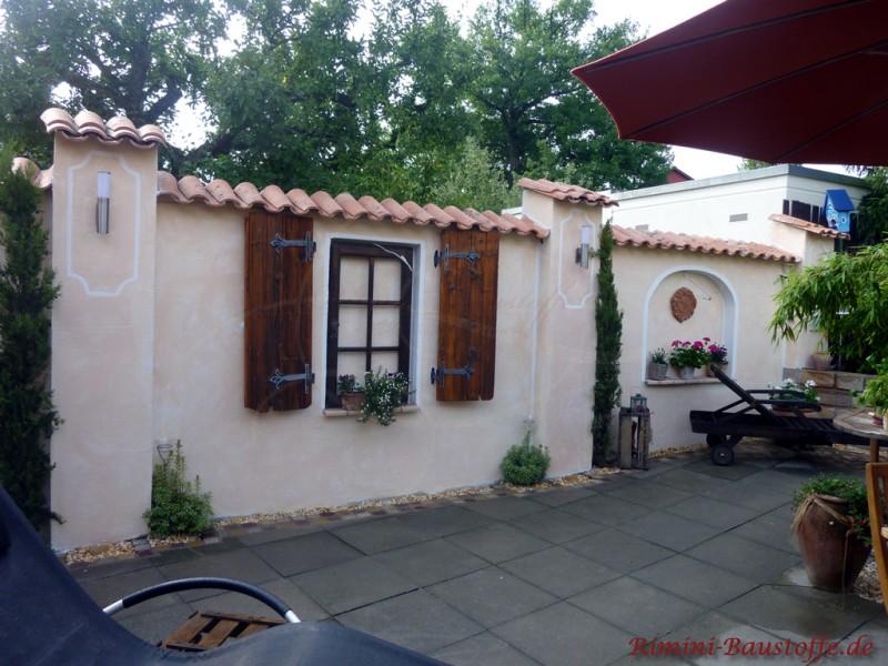 Abgrenzungsmauer mit Dekofenstern und Dekoklappläden im spanischem Stil.