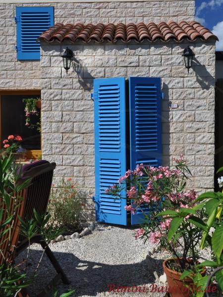 kleiner Erker in Natursteinoptik mit blauen Fensterläden