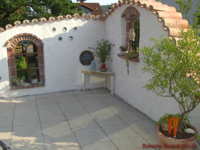 Gewölbte Mauer im weißem Putz mit schmiedereisernen Fenstern und südländischen Halbschalen