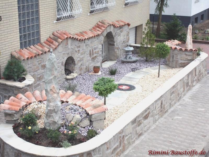 Sehr schöner Schaugarten im mediterranem Stil vor einem Haus. Es sind auch viele Natursteine zu sehen und ein Rondel mit Ziegeln