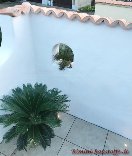weisse verputzte Mauer mit kleinem Fenster