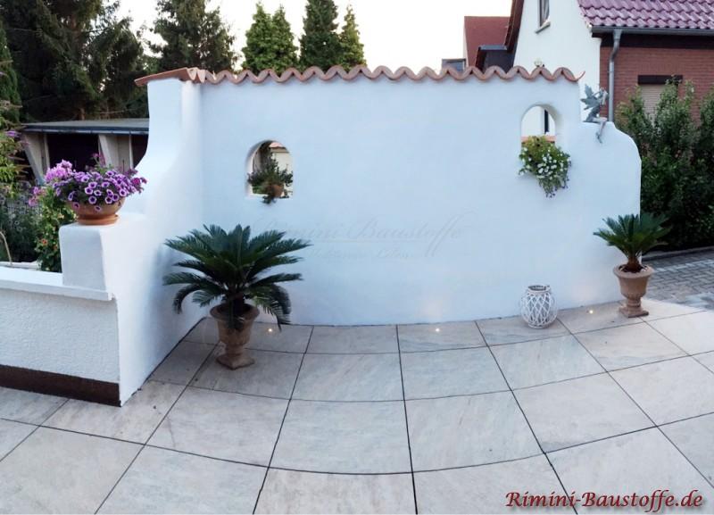 weisse verputze Mauer im Garten mit spanischen Halbschalen abgedeckt