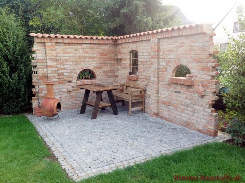 Grillplatz und Sitzecke geschuetzt durch eine mediterran angehauchte Gartenmauer